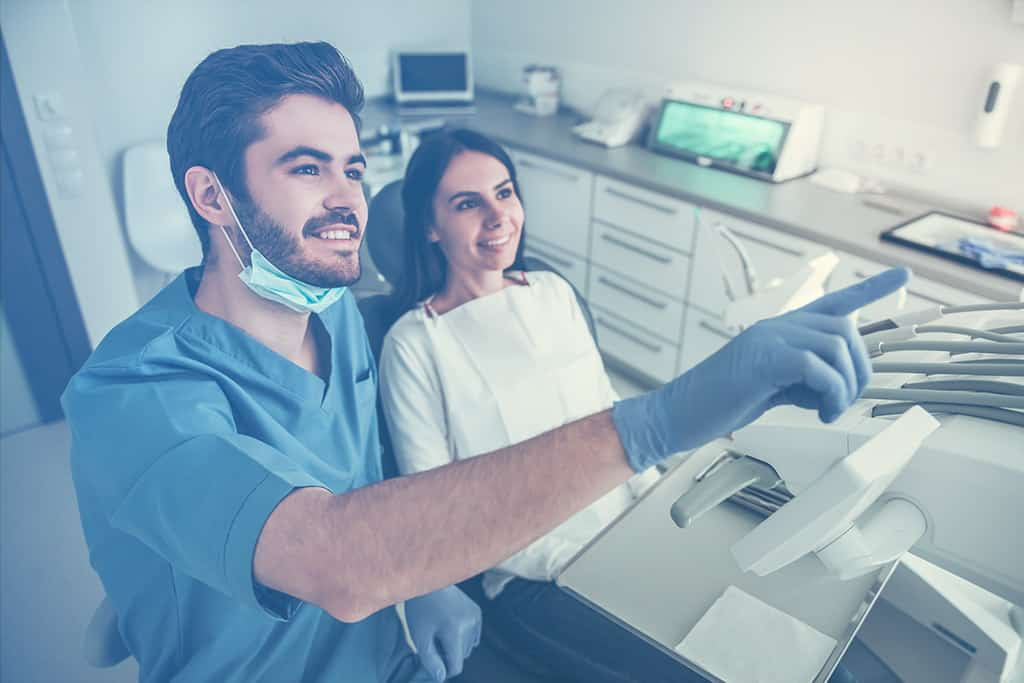 Dentist pointing talking to a patient