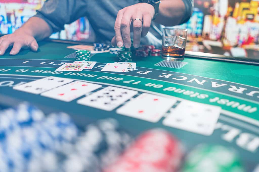 Gambling at casino with cards, chips, and alcohol on the table